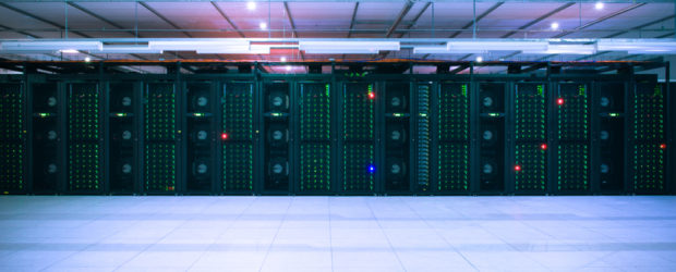 A bank of dark computers fills a room, glowing with many green LED lights.